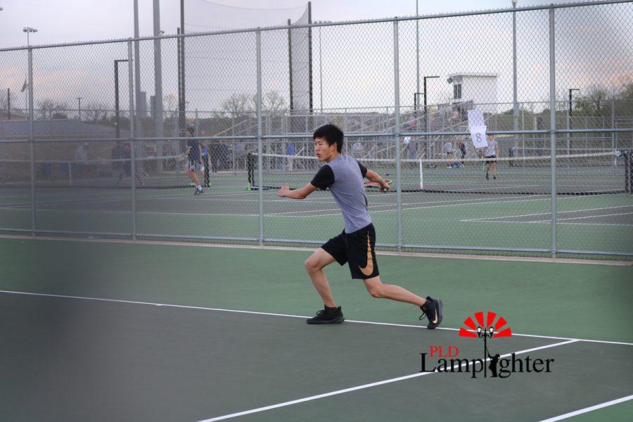 Senior Ben Chen moves towards a ball down the center to hit a forehand.