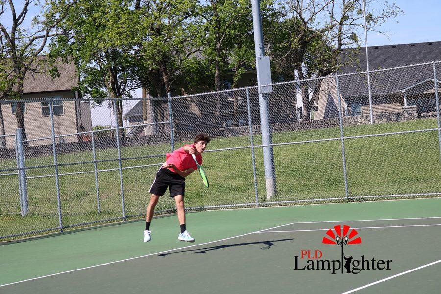 Sophomore Kian Rosenau goes through the finishing motions of his serve.