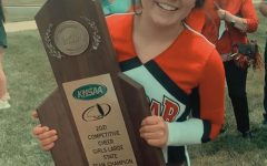 PLD Cheerleader Madelyn Justice holding the 20th State Title Trophy moments after the Dunbar Cheer Team wins.